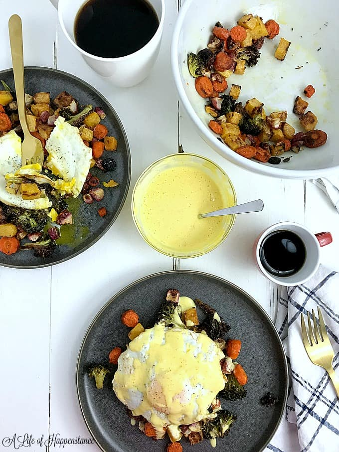 Two plates filled with roasted vegetables and topped with eggs. One of the plates is drizzled with blender hollandaise sauce.