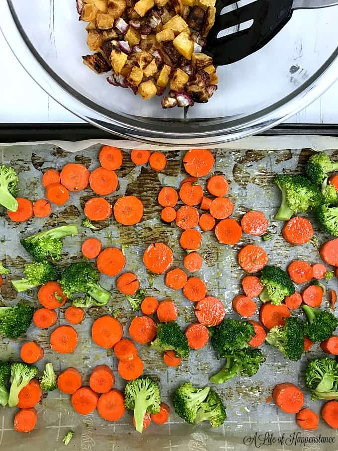 Chopped broccoli and carrots drizzled with olive oil and spread onto a baking sheet.