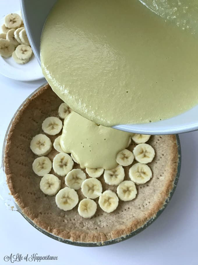 Pouring the dairy free pastry cream (creme patissiere) into the almond flour pie crust.