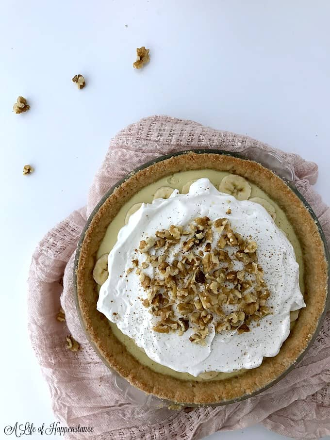 An SCD banana cream pie surrounded by chopped walnuts and a light pink kitchen towel.