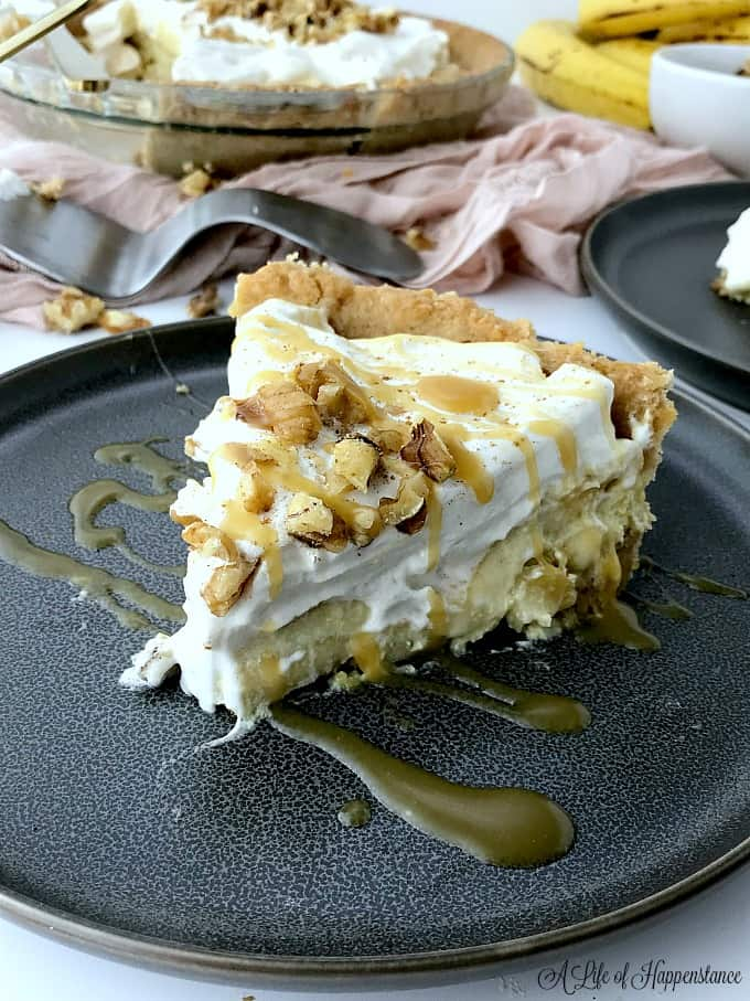 A large slice of paleo banana cream pie on a black plate. The slice of pie is drizzled with a paleo caramel sauce.