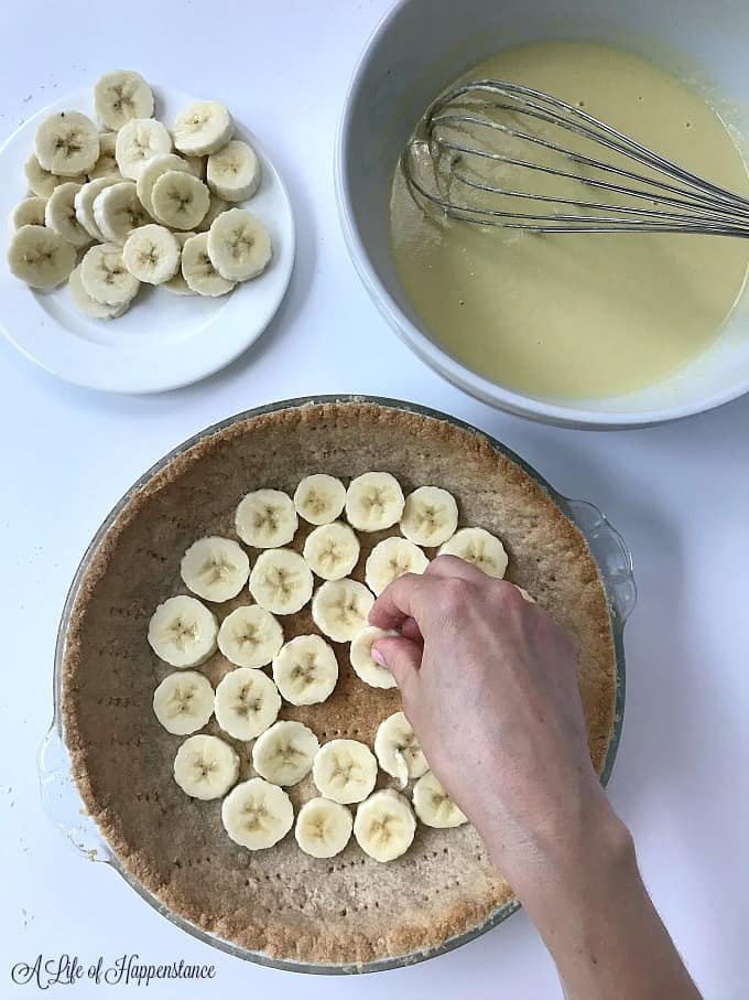 Pressing sliced bananas into the bottom of the baked gluten free pie crust.