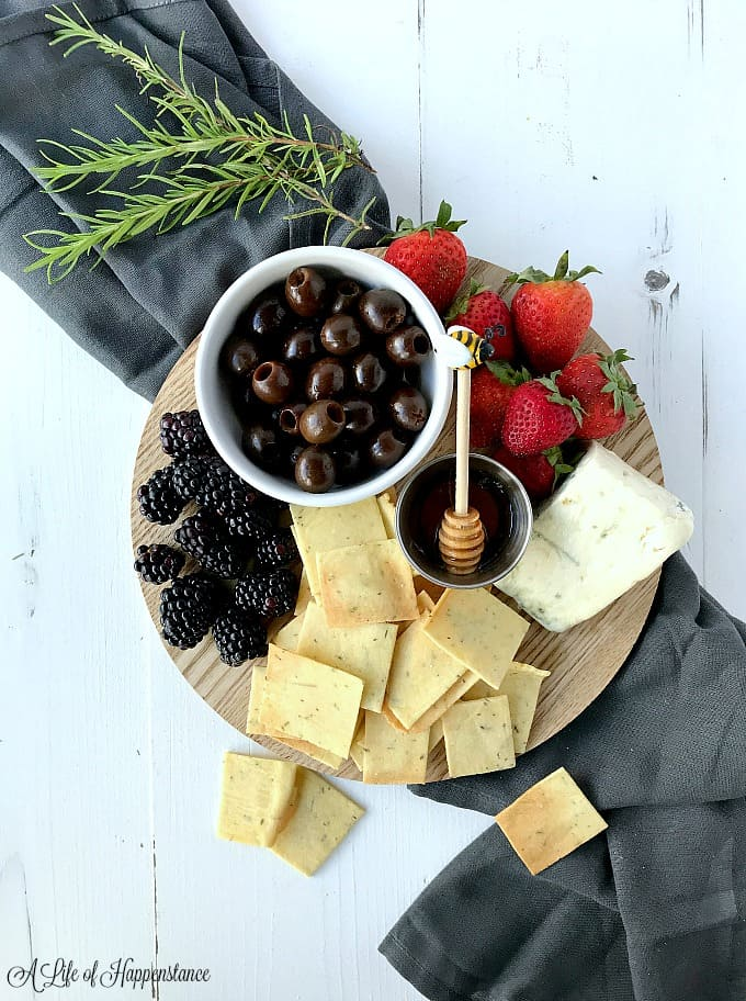 The grain free crackers on a cutting board with cheese, olives, strawberries, and blackberries.