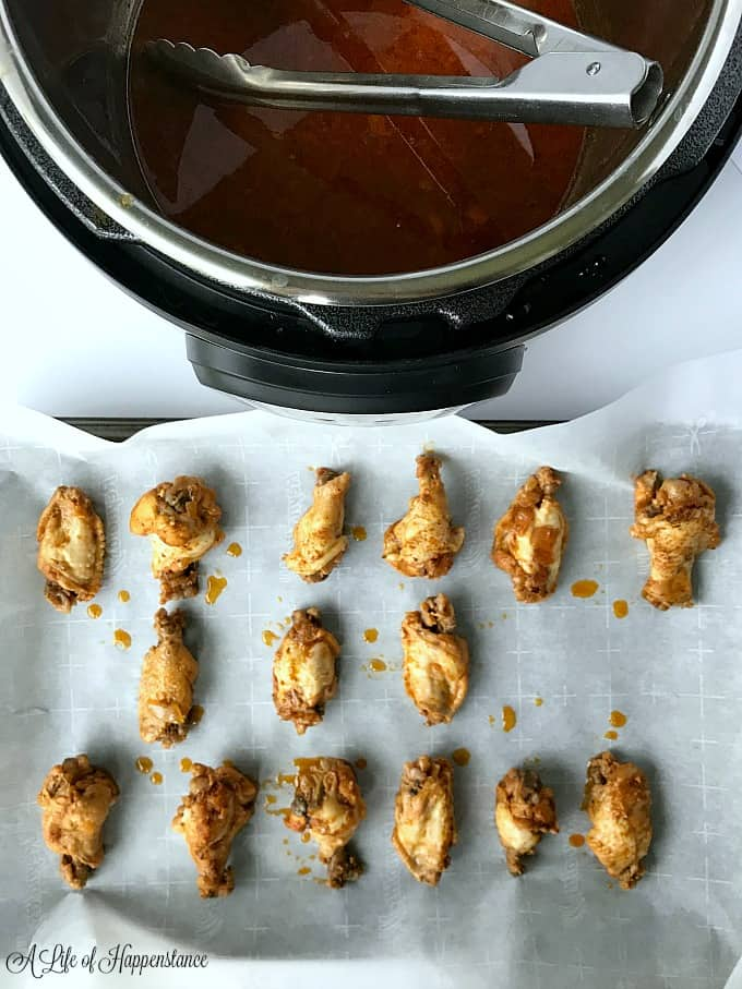 Cooked chicken wings arranges on a parchment lined baking sheet.