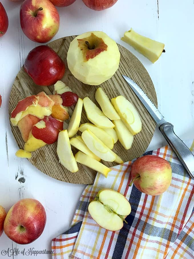 A cutting board with peeled and chopped apples.