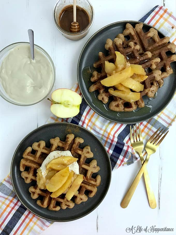 Two plates with gluten free spice waffles and apple compote. A side of cashew cream and honey cinnamon butter.