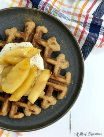 A spice waffle on a black plate topped with an apple compote.