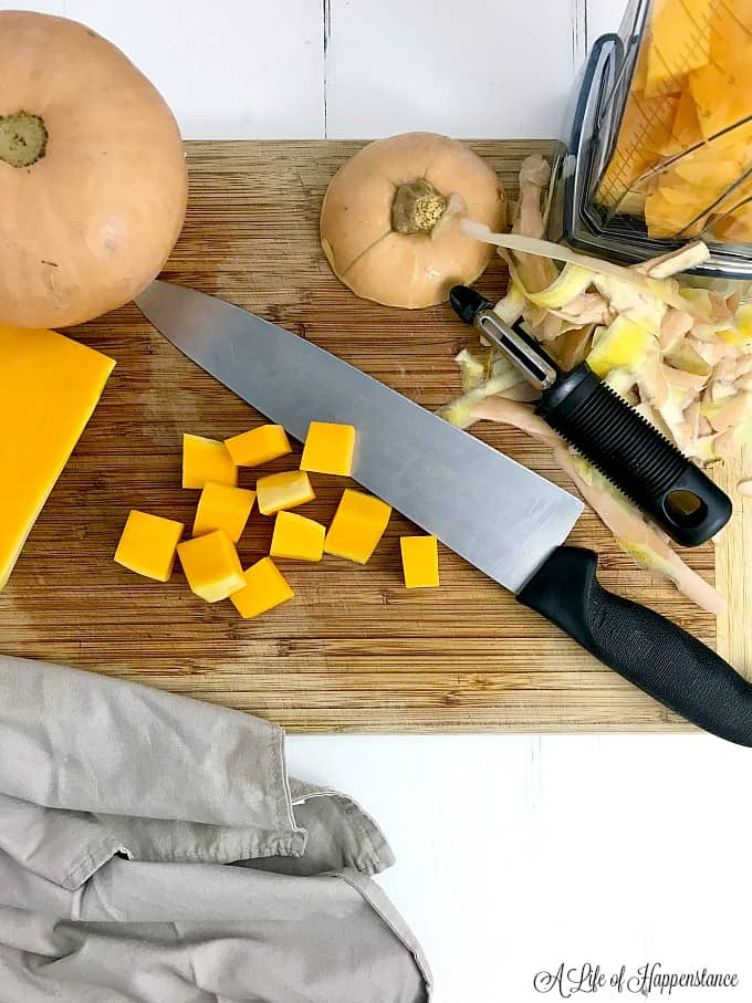 Chopped butternut squash in a blender and on a cutting board.