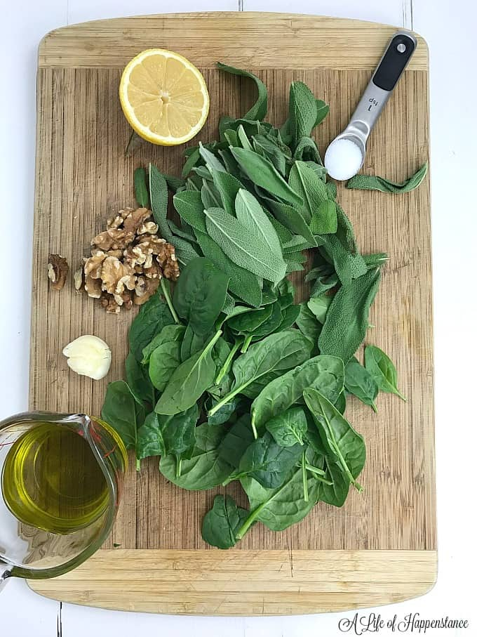 All of the ingredients for vegan pesto sauce on a wood cutting board.
