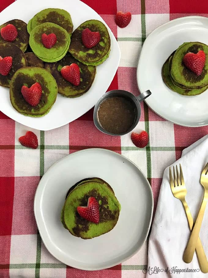 Spinach pancakes on plates with forks and syrup.
