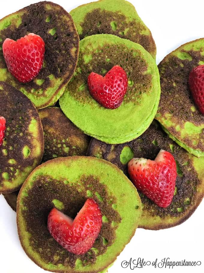 Grinch green pancakes on a white plate topped with strawberry hearts.