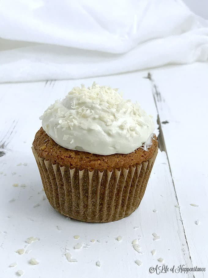 A gluten free coconut cupcake with coconut icing sitting on a white table sprinkled with coconut flakes.