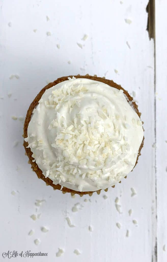 An overhead shot of a gluten free coconut cupcake with coconut icing.