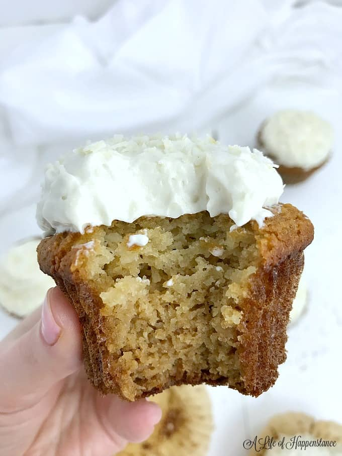 Holding a gluten free coconut cupcakes with coconut icing that has a big bite taken out of it.