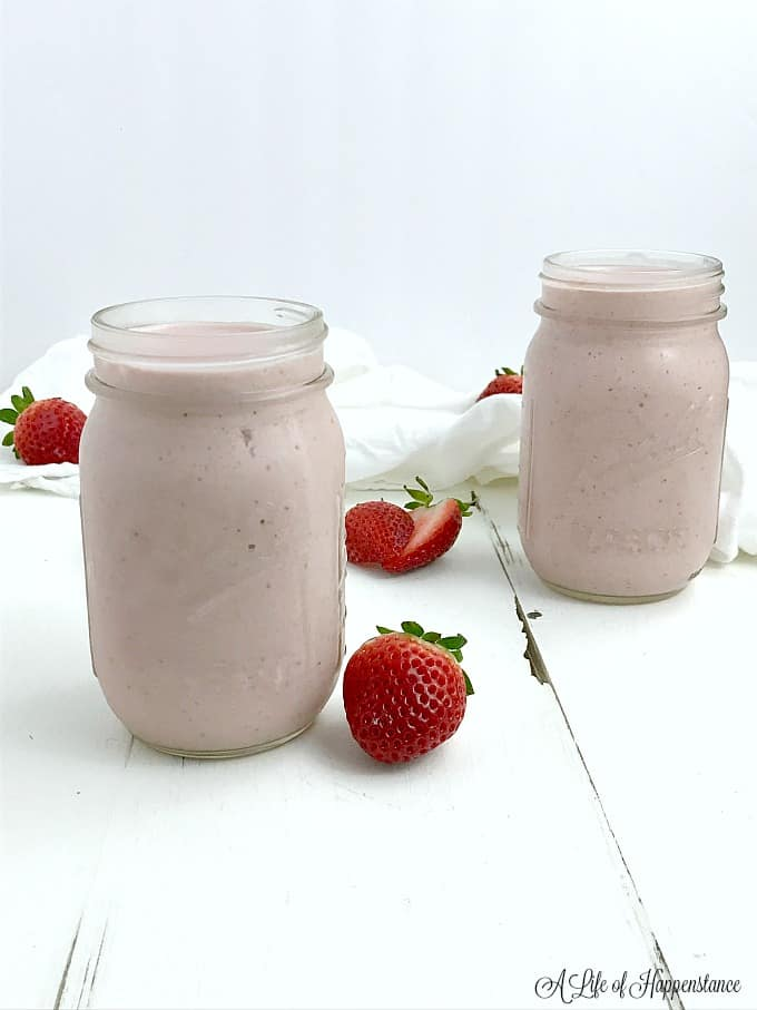 Two mason jars filled with strawberry shortcake smoothie.