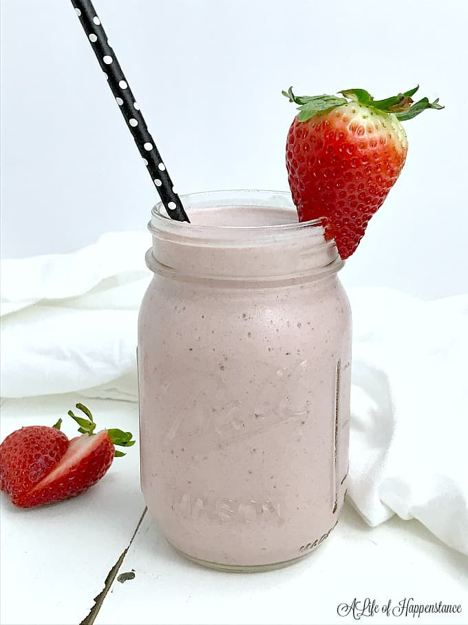 Strawberry shortcake smoothie in a mason jar garnished with a strawberry and straw.