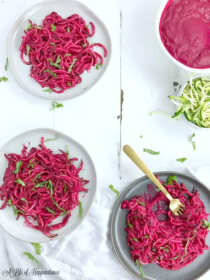 A white table with plates filled with zoodles and beetroot sauce.