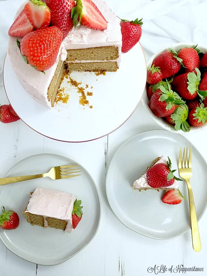 Two white plates with slices of strawberry cake. The rest of the cake on a white cake stand.