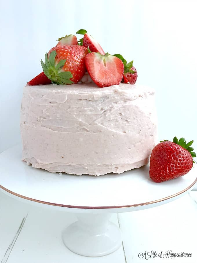 Side view of the strawberry almond flour cake with paleo frosting. Th cake has a mound of strawberries on top.