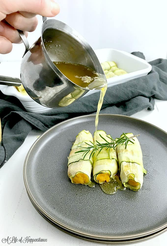 Pouring brown butter rosemary sauce over a plate filled with zucchini cannelloni.