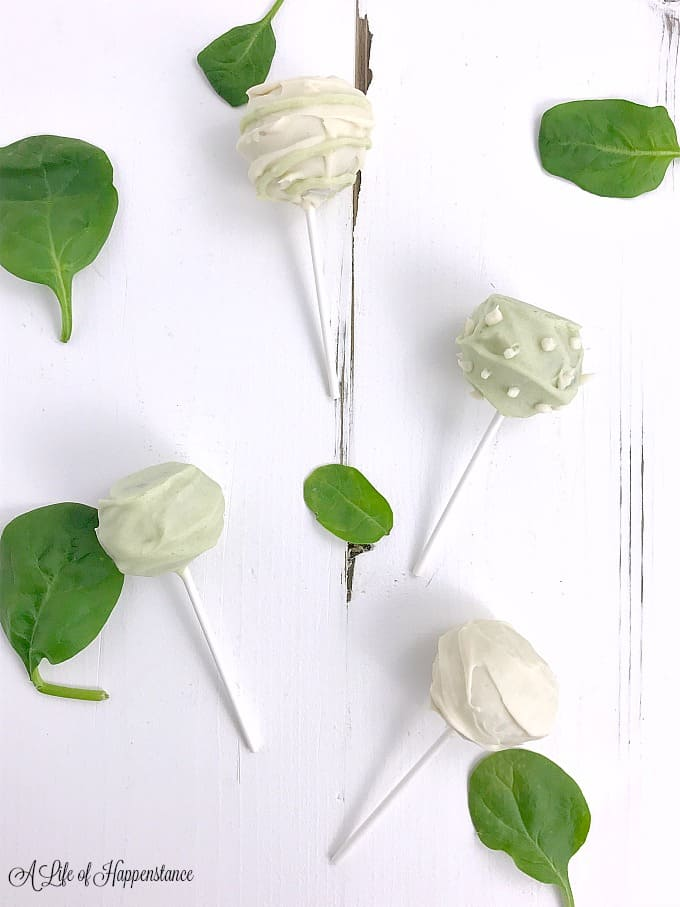 Vanilla cake pops on a white table with spinach leaves.