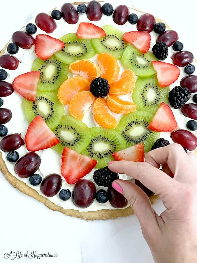 Decorating the gluten free fruit pizza.