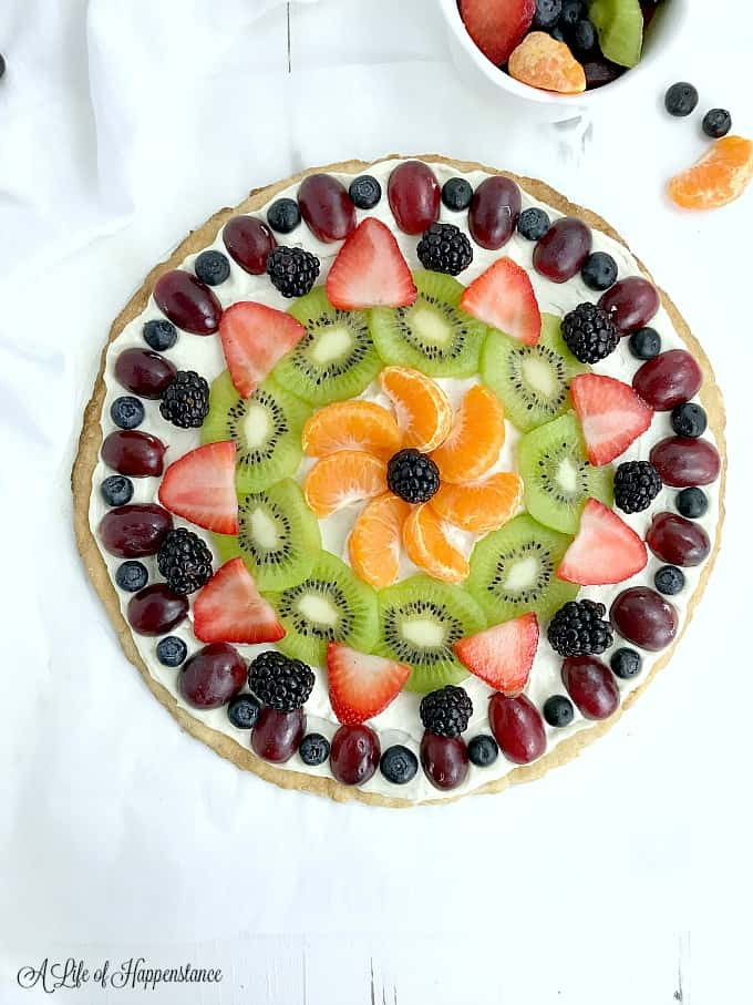 An overhead shot of a fully baked and decorated gluten free fruit pizza.