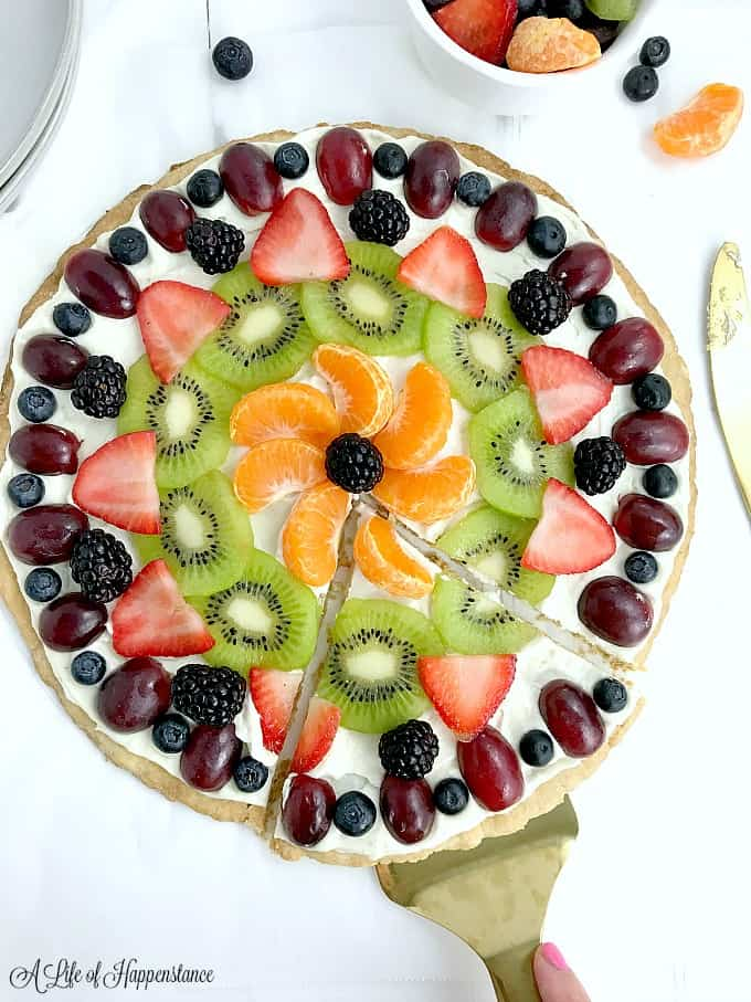 Removing a slice from the easy fruit pizza.