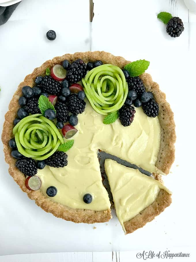 A garnished vanilla custard tart with a slice cut.
