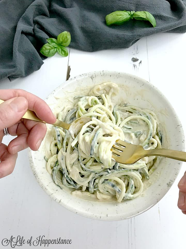 Twirling the alfredo pasta with a fork and spoon.