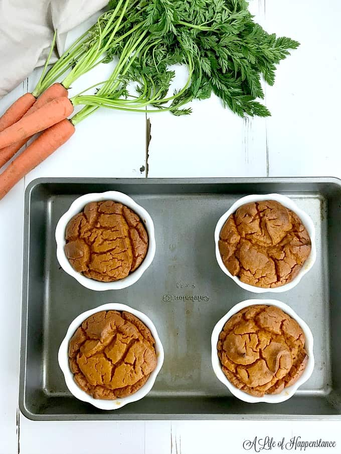 Four ramekins filled with the paleo carrot souffle recipe on a baking sheet.