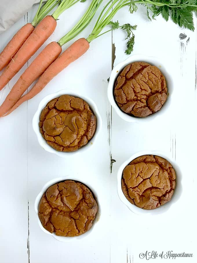 Four white ramekins with paleo carrot souffle.