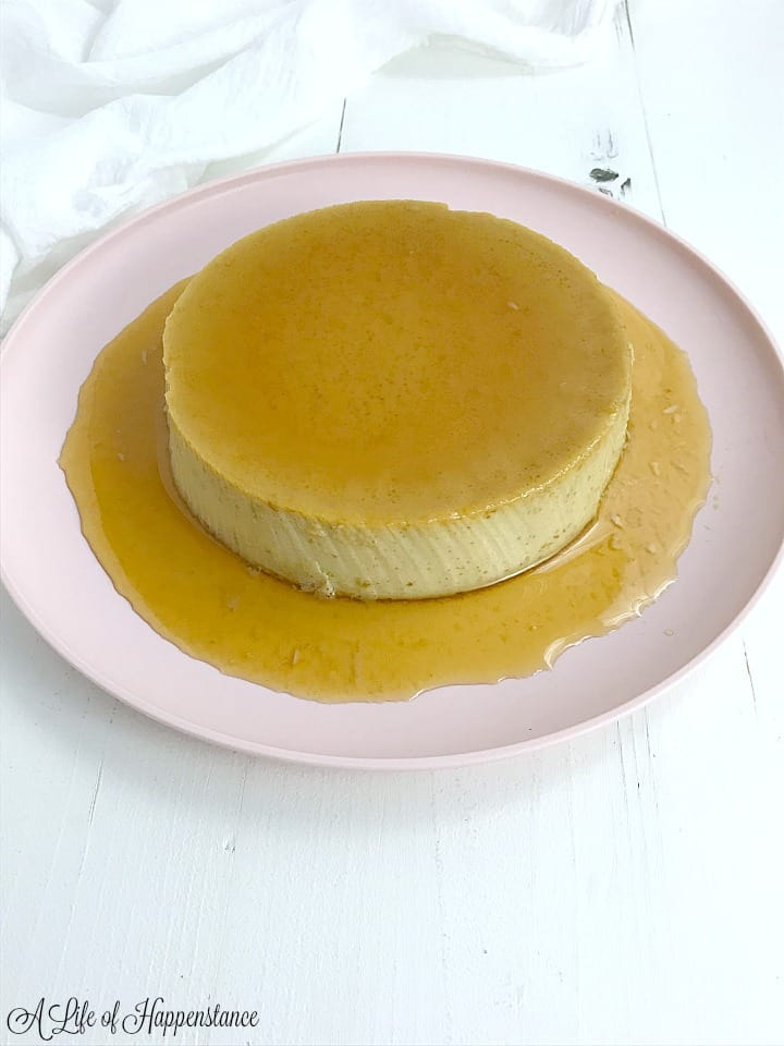A dairy free flan covered in honey caramel sauce on light pink plate.