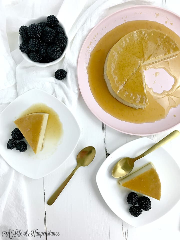 Two slices of almond milk flan on white plates with blackberries. The rest of the flan is on a light pink plate.