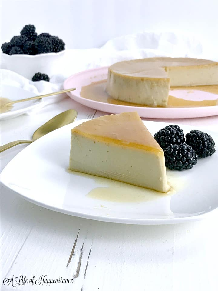 A slice of Cuban flan on a white plate with a few blackberries.