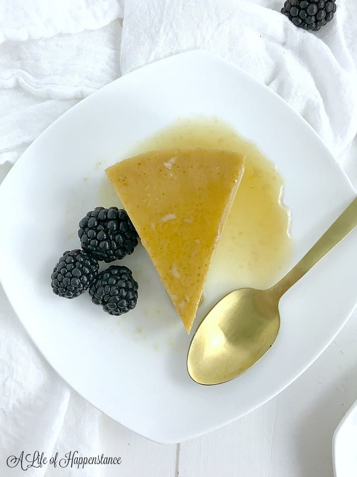 Once slice of Cuban flan on a white plate with blackberries and a gold spoon.