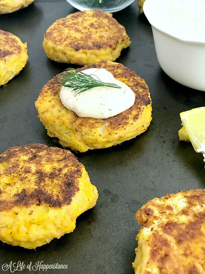 A side view of a tuna cake topped with remoulade on a baking sheet.