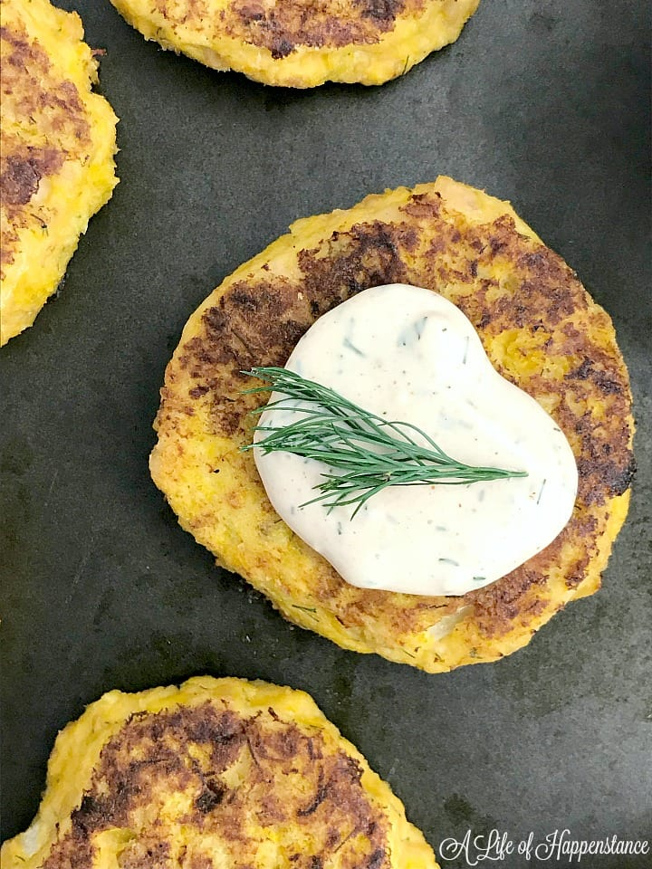 A tuna cake on a baking sheet topped with remoulade sauce and a small sprig of dill.