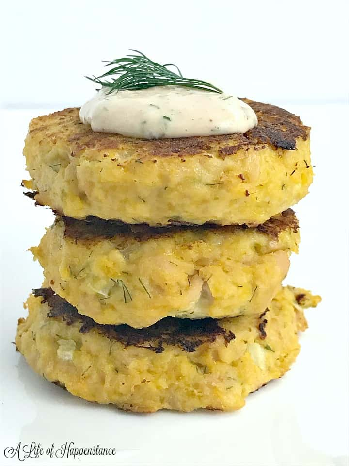 Three paleo tuna cakes stacked on top of each other on a white plate.