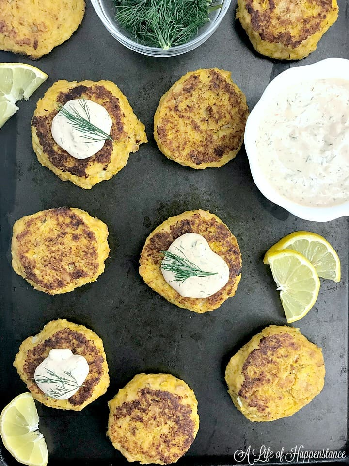 A baking sheet filled with tuna cakes. A few are topped with the easy remoulade sauce.