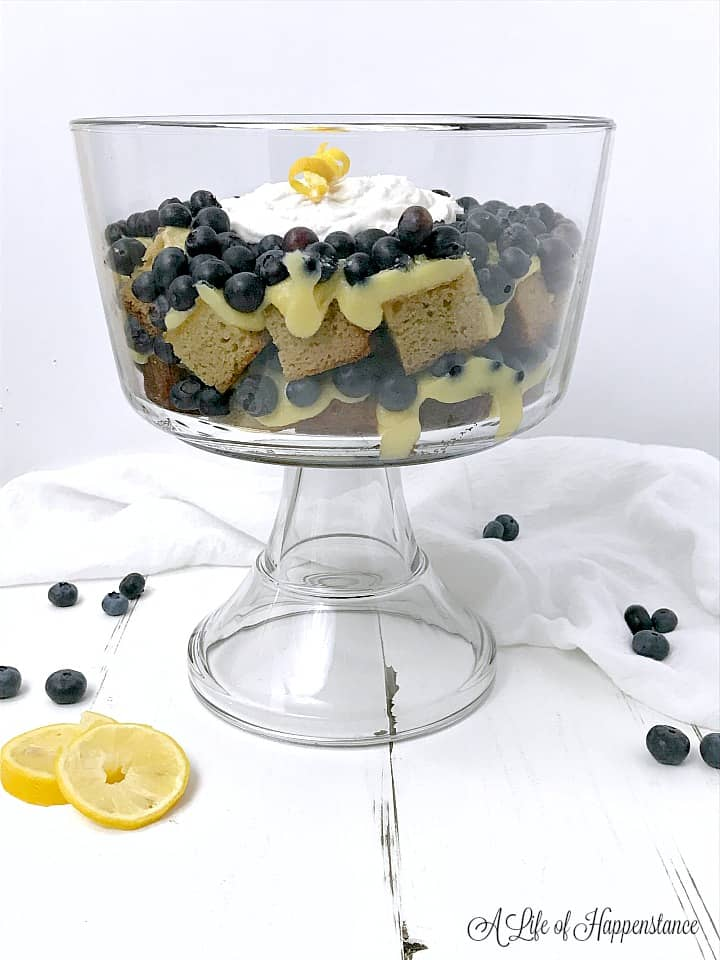 Blueberry lemon trifle in a clear glass trifle dish on a white table surrounded by blueberries and sliced lemons.