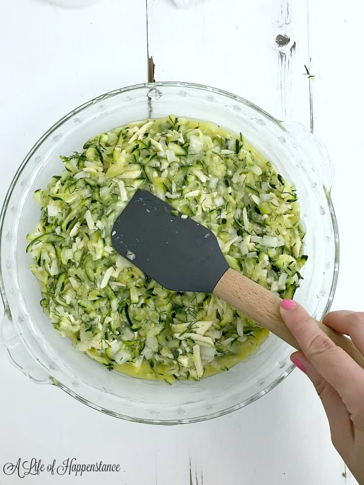 Using a grey spatula to spread the zucchini mixture in the pie dish.