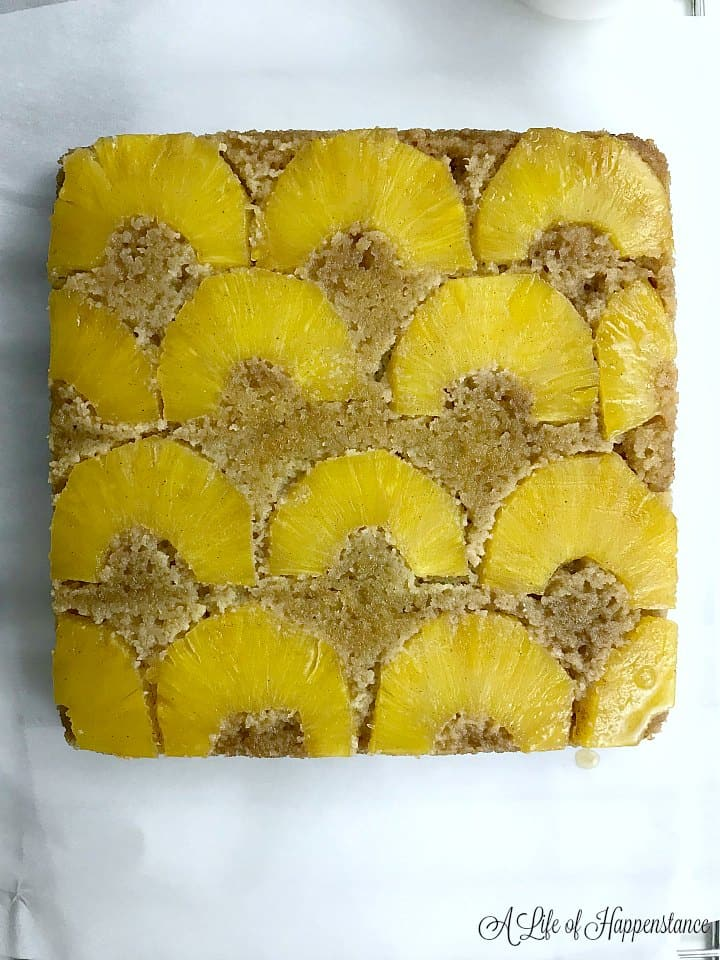 A fully baked paleo pineapple upside-down cake on white parchment paper.