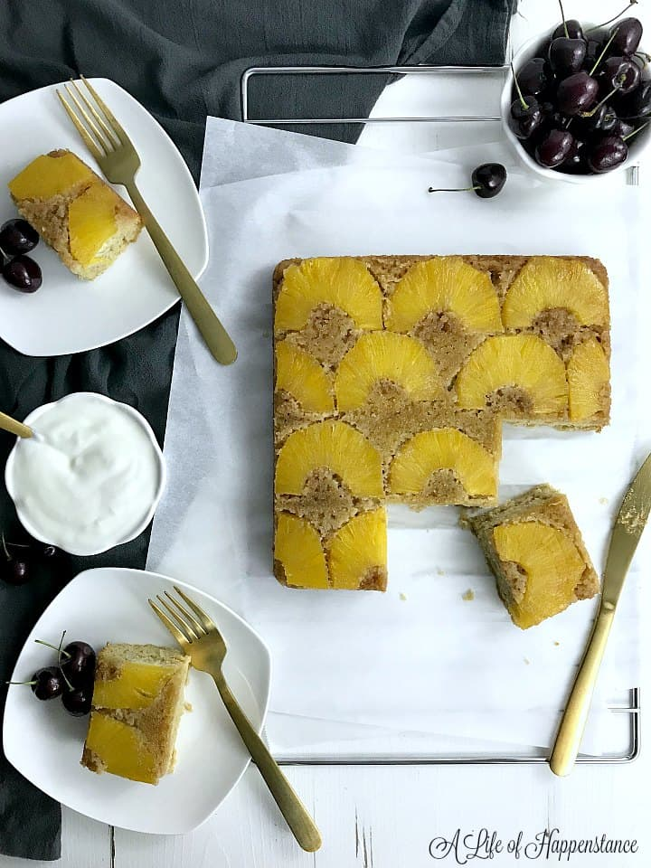 Paleo pineapple upside-down cake on a cooling rack with a piece cut. Two pieces of cake on white plates.