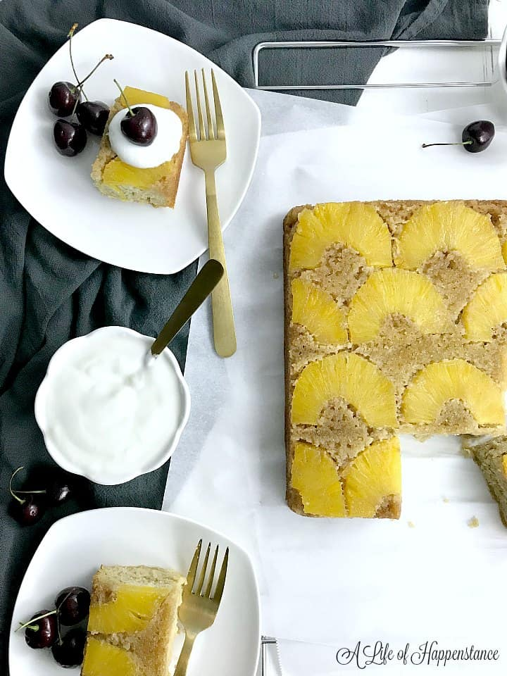 Overhead shot of the pineapple cake with two pieces on white plates. One piece of cake is topped with coconut whipped cream and fresh cherries.