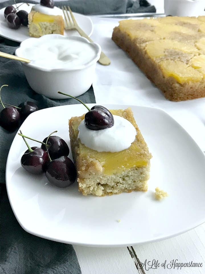 A slice of pineapple cake on a white plate topped with coconut whipped cream and fresh cherries. The rest of the cake and a bowl of whipped cream is in the background.