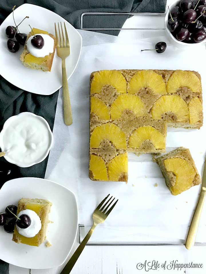 Pineapple upside-down cake on a cooling rack with three pieces cut. Two pieces on white plates topped with coconut whipped cream and fresh cherries.