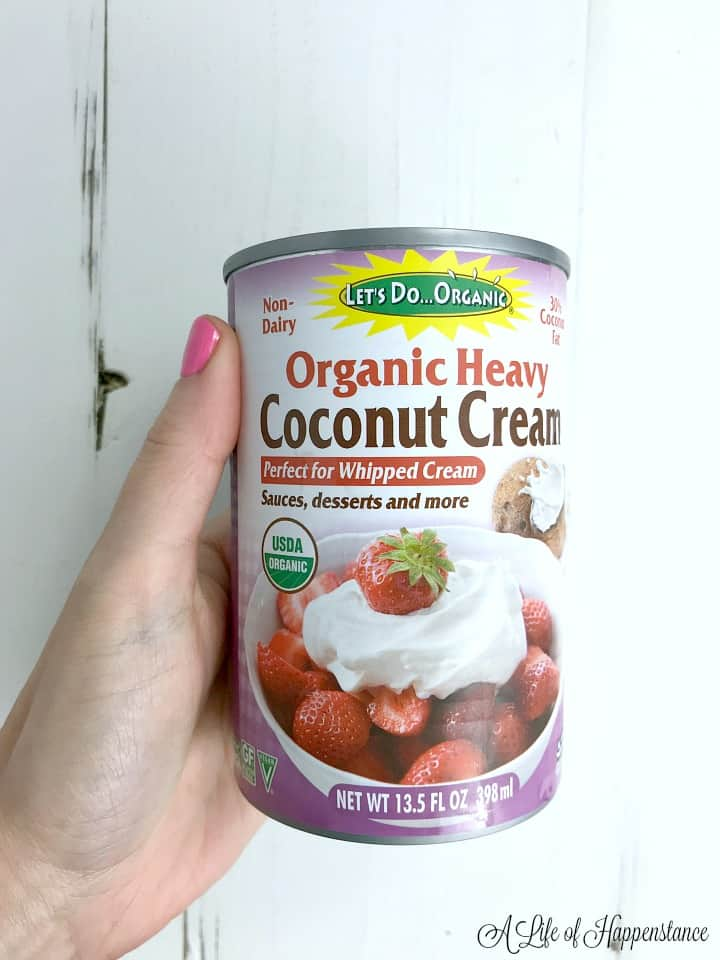A hand holding a can of organic heavy coconut cream.