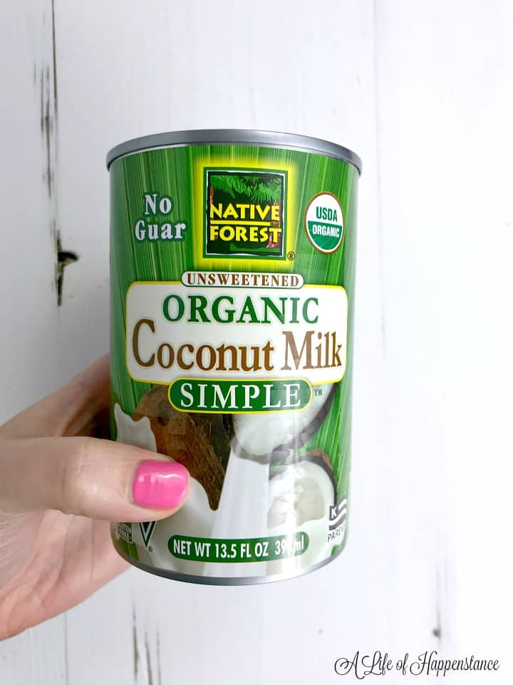 A hand holding a can of organic coconut milk.