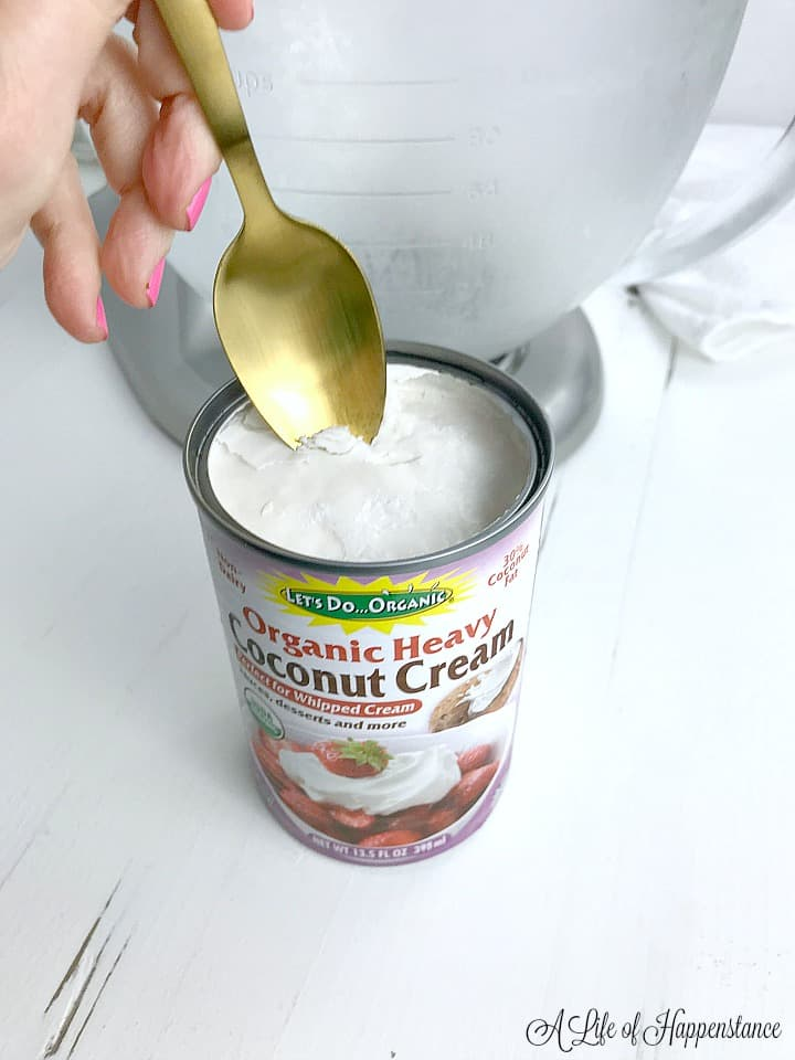 A hand holding a spoon scooping  coconut cream out of a can.